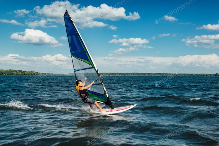the athlete rides the windsurf over the waves on the lake