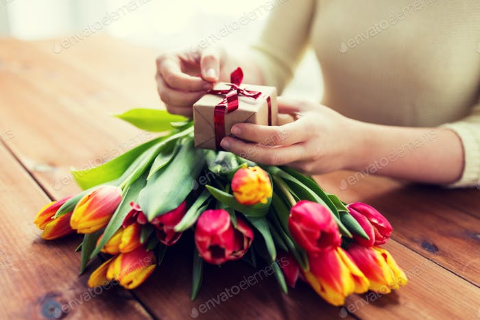 close up of woman with gift box and tulip flowers