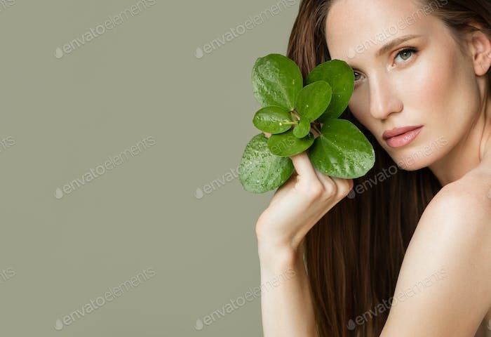A Beautiful Woman Holds A Green Leaves In Her Hands. Cleanliness And Care.