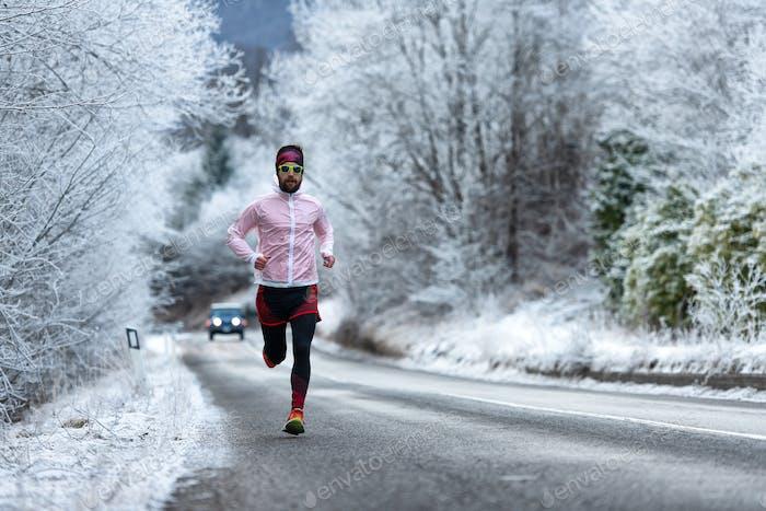 Läufer auf eiskalter Straße auf den Alpen