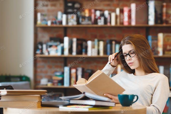 Junge Frau, die zu Hause mit einer Tasse Kaffee studieren