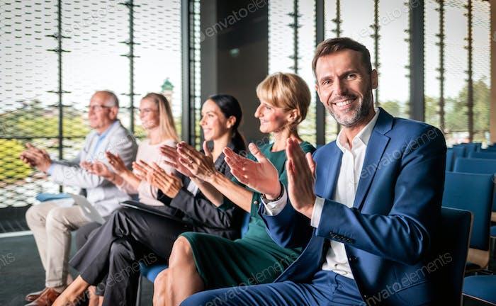 Glückliches Publikum applaudiert Redner auf der Business-Konferenz