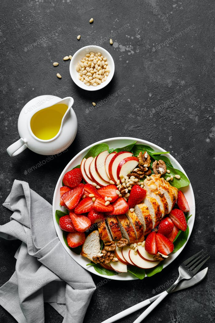 Grilled chicken breast and strawberry salad with red apples, fresh spinach and nuts
