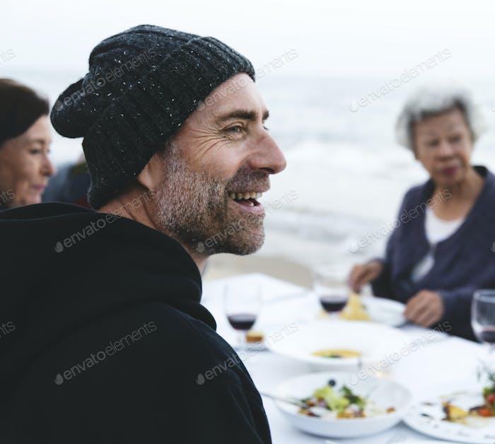 Reife Freunde trinken Wein am Strand