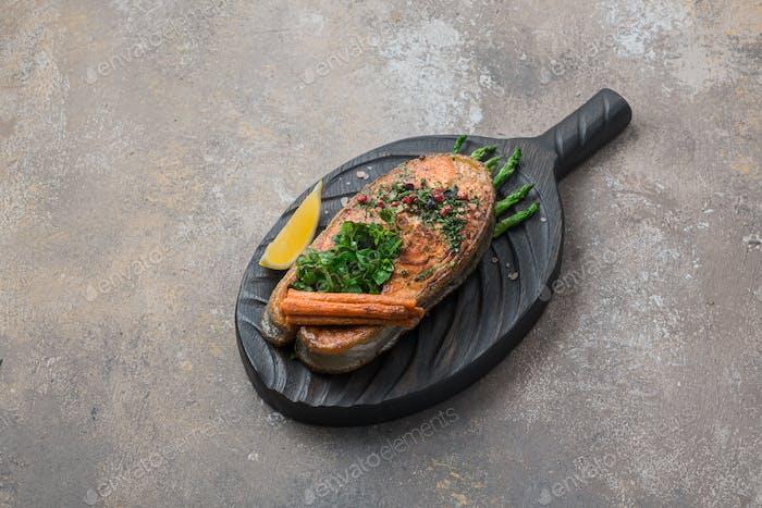 Gebratenes Lachssteak mit Gemüse auf Holzbrett, Kopierraum