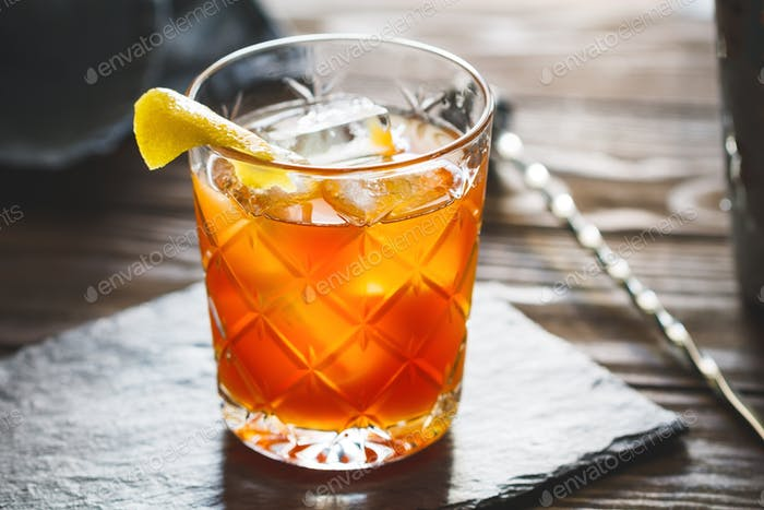 The alcoholic Surfer on Acid cocktail in a old-fashioned glass with a lemon wedge.