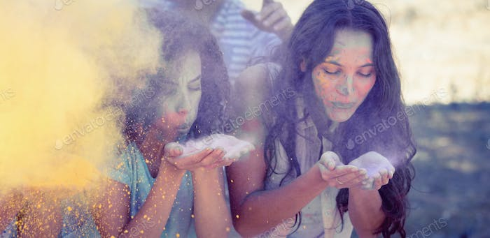 Young women having fun with powder paint on a sunny day