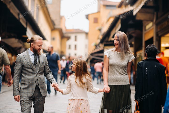 A happy family of three walking in Florence.Family walk of the family in Italy.Tuscany