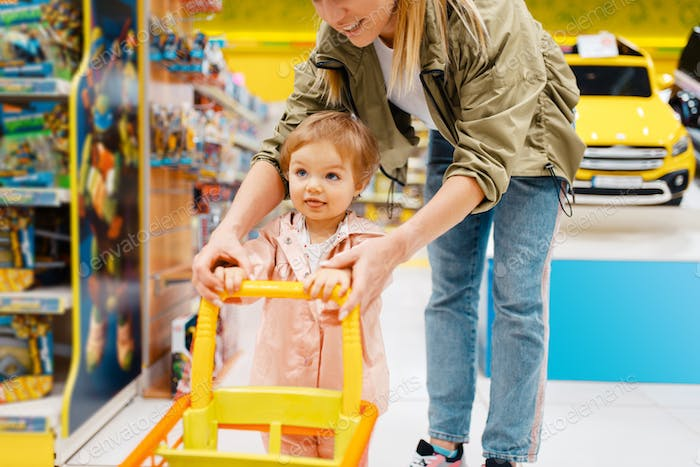 Happy mother with little daughter in kids store