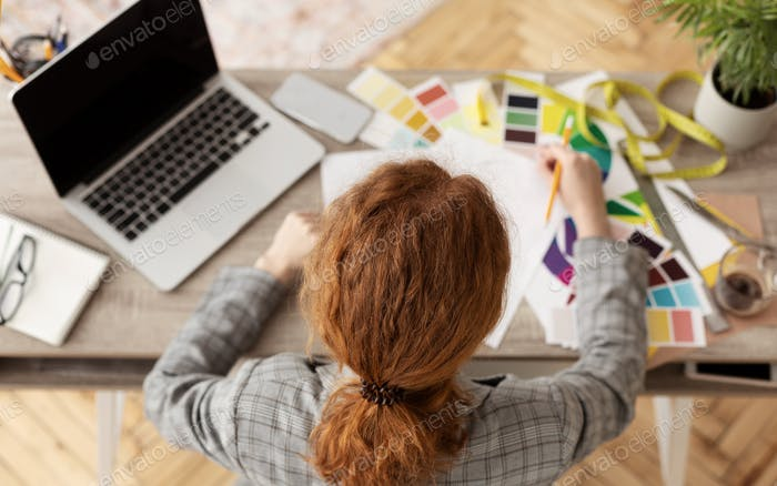 Young female fashion stylist working at home