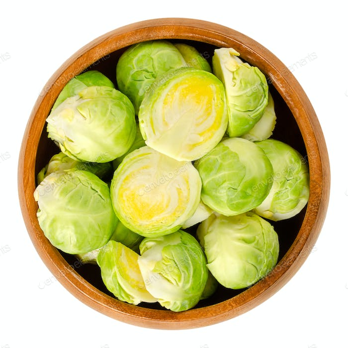 Fresh Brussels sprouts in wooden bowl over white