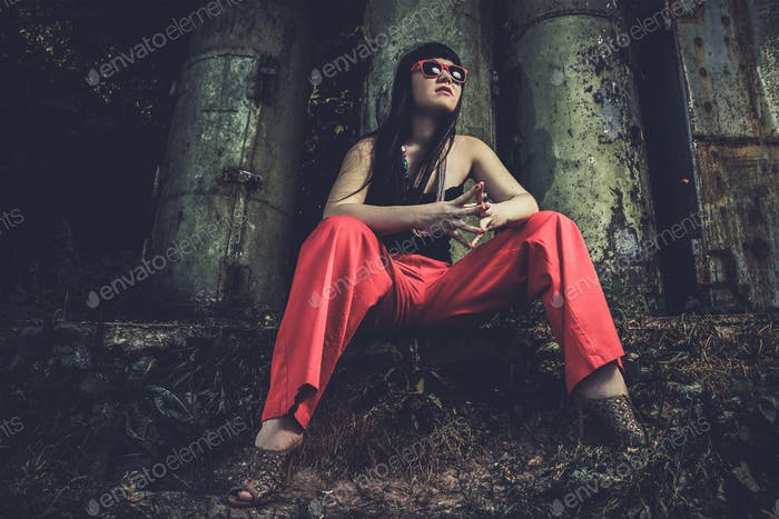 girl in red pants and glasses over industrial background