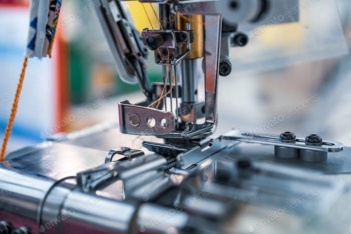 Профессиональная швейная машина крупным планом. Современная текстильная промышленность.
