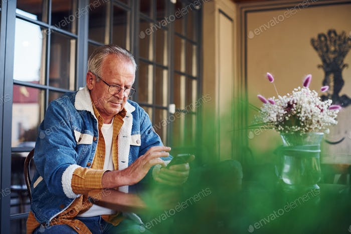 Стильный старший в модной одежде и в очках сидит в кафе с телефоном