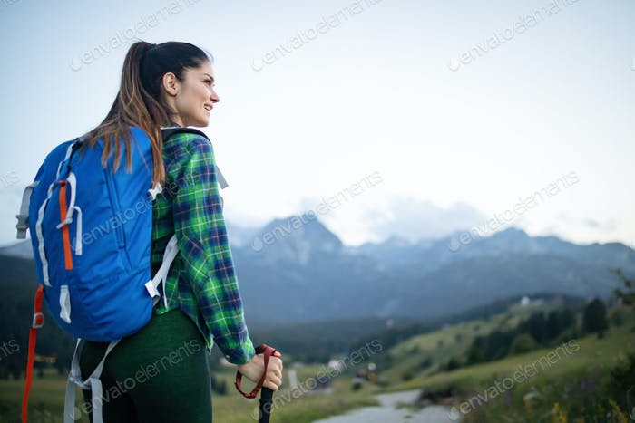 Girl traveler hiking with backpack at rocky mountains landscape. Travel lifestyle concept adventure