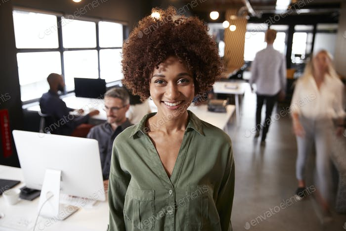 Millennial black female creative standing in a busy casual office, smiling to camera
