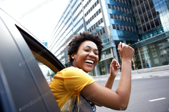 Excited woman looking out the car window with her arms raised