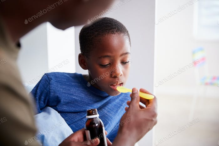 Father Giving Sick Son Ill In Bed Medicine From Bottle