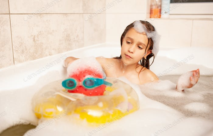 Funny little girl bathes in a bath with foam and plays life saving ball