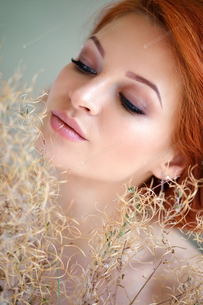 Portrait of young beautiful redhaired woman with dried flowers