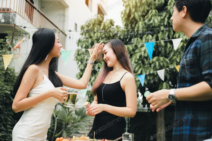 Teenagers are enjoying a garden party at home and holding the beer glass in hand.