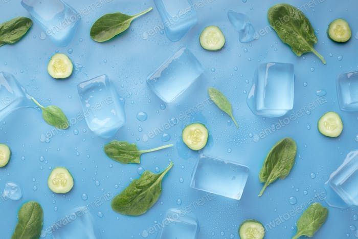 Fresh summer wallpaper with cucumbers and ice cubes on blue