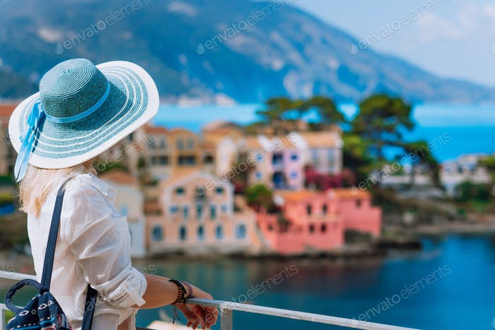 Tourist woman in blue sunhat and white clothes enjoying top view of colorful tranquil village Assos