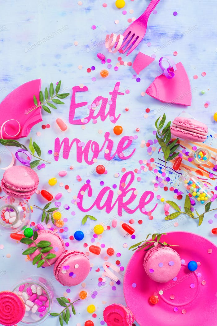 Party concept with Eat more cake paper text, candies, sweets, confetti and macarons. Colorful