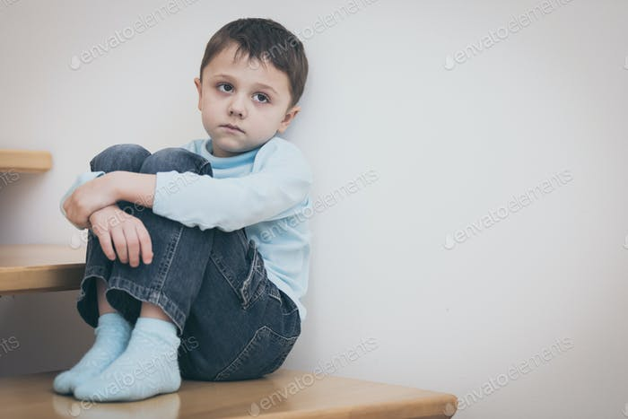 ein trauriger kleiner Junge sitzt auf der Treppe im Haus am Tag tim