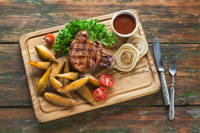 Grilled pork steak with potato wedges top view