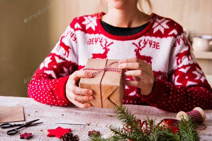 Unrecognizable woman wrapping a Christmas present.