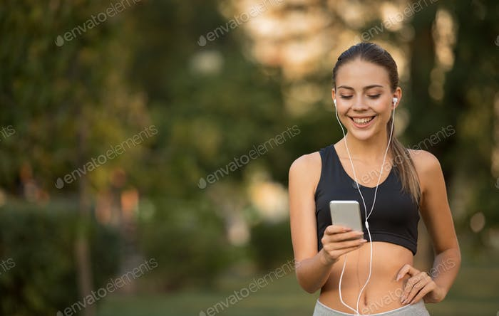 Cheerful active sporty girl choosing music for training