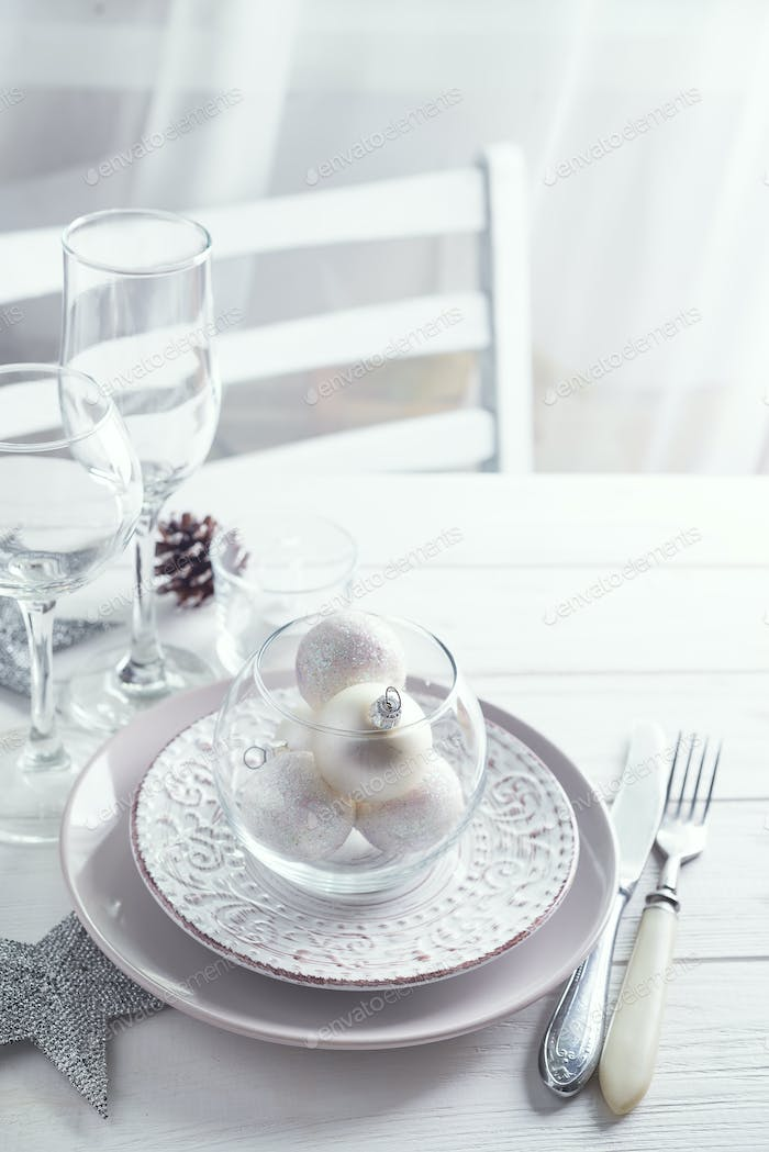 Silver and white Christmas Table Setting with christmas decorations above light window