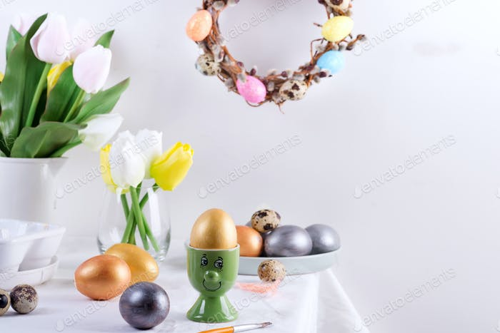 Holiday composition of served table with golden egg in a green cup as a face , baked cookies, fresh