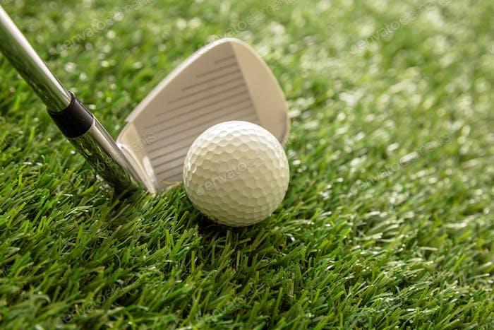 Golf stick and ball on green grass golf course, close up view.