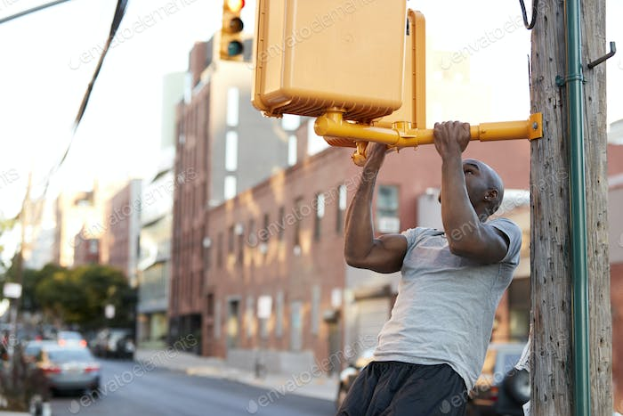 Young black man doing chin ups from crossing light in street