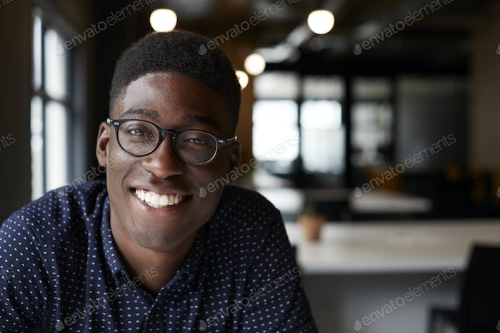 Millennial black male creative sitting at a desk in an office smiling to camera, close up