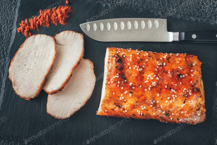 Baked meat with paprika on the black sone board