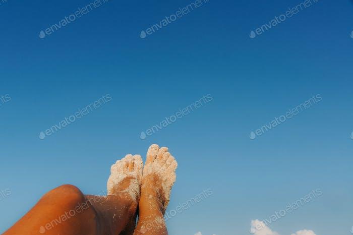 tan female feet in white sand