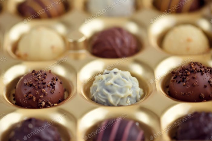 Assorted of chocolate candies in gold gift box. Selective focus
