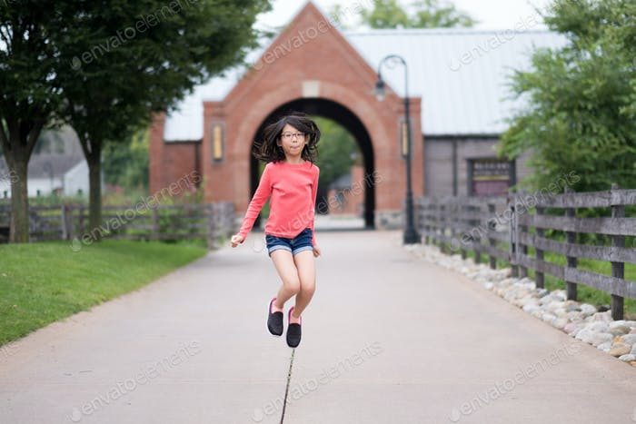 Smiling little Asian girl jump up in the park