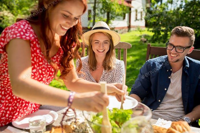 glückliche Freunde mit Abendessen auf Sommergarten Party