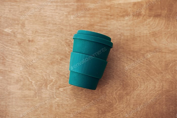 Stylish reusable eco coffee cup on wooden background