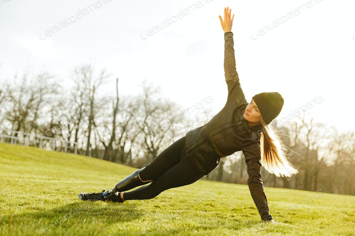 Image of sporty handicapped woman in black tracksuit, exercising