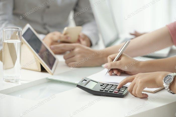 Crop woman using calculating machine