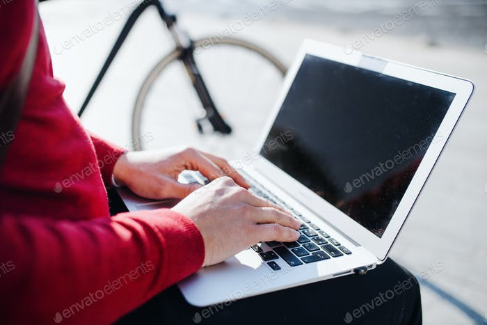 A midsection of businessman sitting on bench in city, using laptop. Copy space.