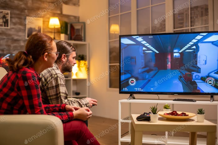 Couple playing video games on big screen TV in the living room late at night