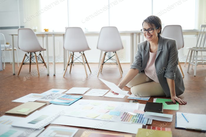 Cheerful Businesswoman Planning Project on Floor