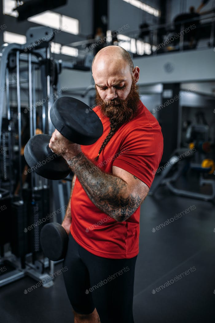 Athlete doing exercise with dumbbells in gym