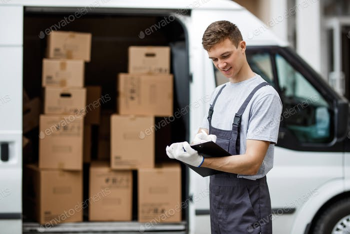 A young handsome smiling worker wearing uniform is standing next to the van full of boxes holding a
